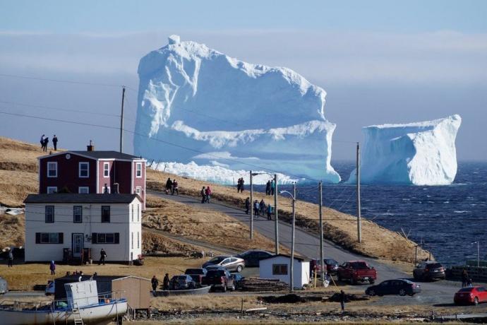 Граждане маленького канадского городка фотографируются нафоне гигантского айсберга